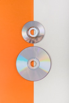 Uma visão geral de discos compactos em um fundo duplo laranja e branco