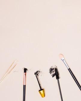 Uma visão geral de pinças; pincel de maquiagem e escova de rímel isolado no fundo bege