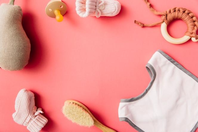 Uma visão geral do babador do bebê; chupeta; meia; escova; pêra recheada e brinquedo em fundo de pêssego
