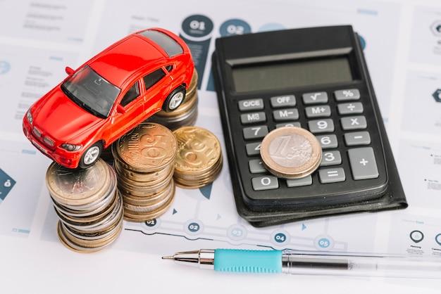 Uma visão geral do carro sobre a pilha de moedas; calculadora e caneta sobre o modelo de infográfico