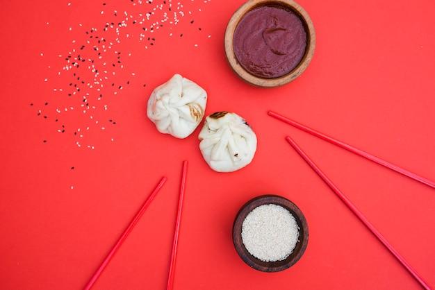 Uma visão geral do molho; dumplings; sementes de gergelim e pauzinhos no pano de fundo vermelho