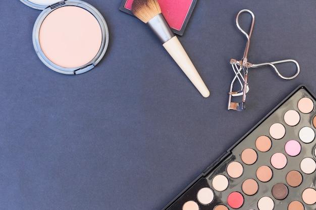 Uma visão geral do pincel de maquiagem; blusher; paleta de sombra e encrespador em pano de fundo azul