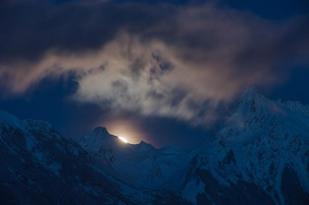 Uma visão noturna dos alpes cobertos de neve na áustria