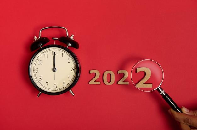 Uma visão plana da meia-noite em um mostrador de despertador preto ao lado de numerais de madeira e uma mão cortada segurando uma lupa que mostra o ano de 2022. conceito de ano novo isolado sobre fundo vermelho