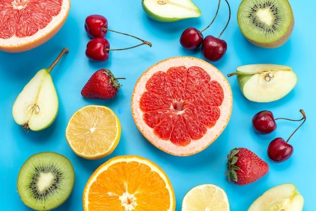 Uma visão superior da composição de frutas coloridas de frutas maduras e fatiadas em azul, cor de vitamina de frutas