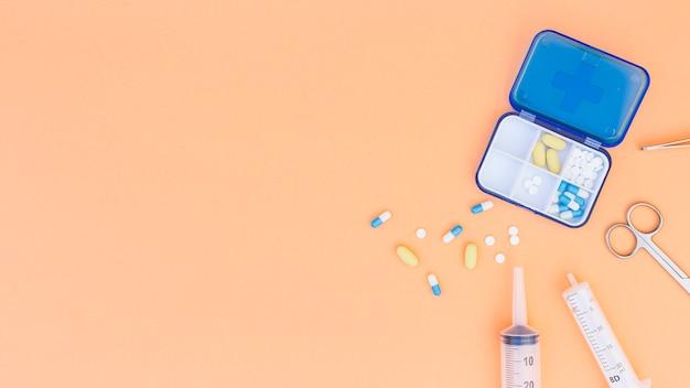 Uma vista aérea da caixa de comprimidos médicos; seringa; tesoura e pinça em fundo bege