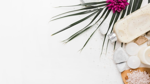 Uma vista aérea da folha de palmeira; flor; pedra; esfoliação corporal; velas e sal de ervas no pano de fundo branco