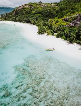 Uma vista aérea da praia de areia intocada com palmeiras e barco solitário. seychelles