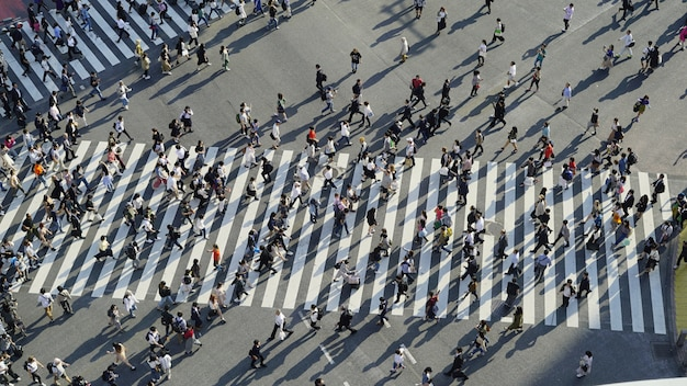 Uma vista aérea das multidões que cruzam o cruzamento mexido em shibuya (tóquio, japão)