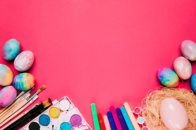 Uma vista aérea de ovos da páscoa pintados da aguarela; pincéis de pintura; caneta de ponta de feltro e ovos de páscoa no pano de fundo rosa