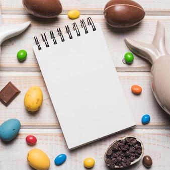 Uma vista aérea do bloco de notas espiral em branco com ovos da páscoa; doces e chips de chocolate na mesa de madeira