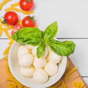 Uma vista aérea do mozzarella italiano com folha da manjericão; tomates e massa fusilli