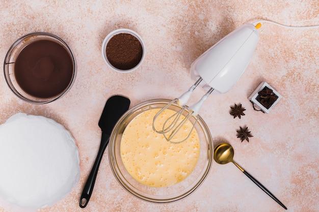 Uma vista aérea do xarope de chocolate; cacau em pó; anis; espátula; concha e misturador elétrico no plano de fundo texturizado