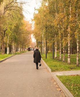 Uma vista da parte de trás de uma mulher adulta vestida com roupas pretas e caminhando por um beco de folhagem amarela dourada de árvores de outono outono na estrada em moscou.