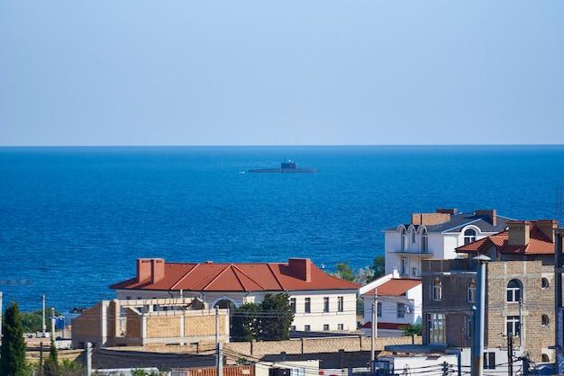 Uma vista das casas em construção, o céu e um submarino no mar.