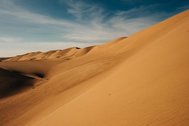 Uma vista das dunas do deserto ao pôr do sol