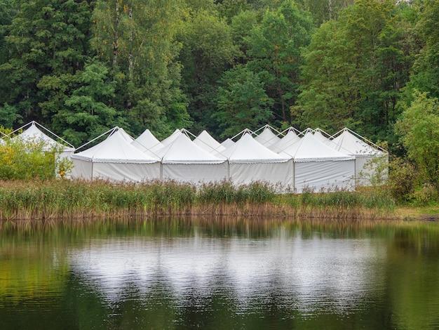 Uma vista das tendas brancas junto à água.