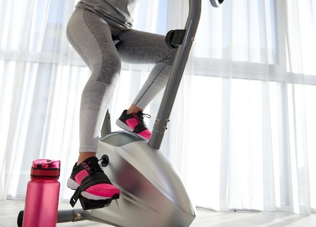 Uma vista de baixo sobre as pernas de uma mulher esportiva girando em uma bicicleta
