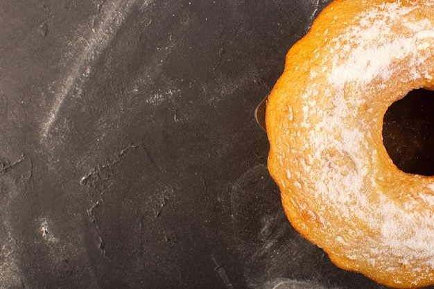 Uma vista de cima assada em um bolo redondo com açúcar em pó no fundo de madeira