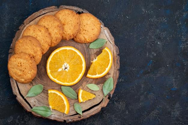 Uma vista de cima biscoitos com sabor de laranja com fatias de laranja fresca no fundo escuro.