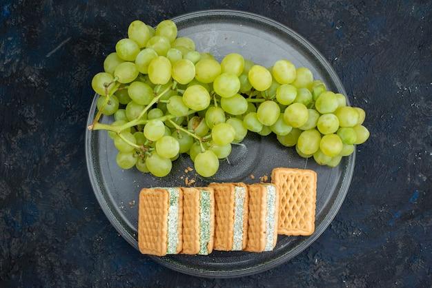 Uma vista de cima biscoitos com sabor de uva biscoitos recheados com uvas verdes frescas dentro de um prato no fundo escuro.