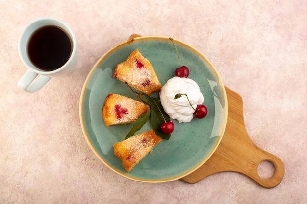 Uma vista de cima bolo de frutas assado delicioso fatiado com cerejas vermelhas dentro e açúcar em pó dentro de um prato redondo verde com chá rosa