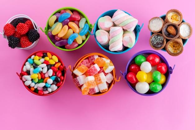 Uma vista de cima bombons e marmeladas coloridas e deliciosas dentro de cestas na cor rosa