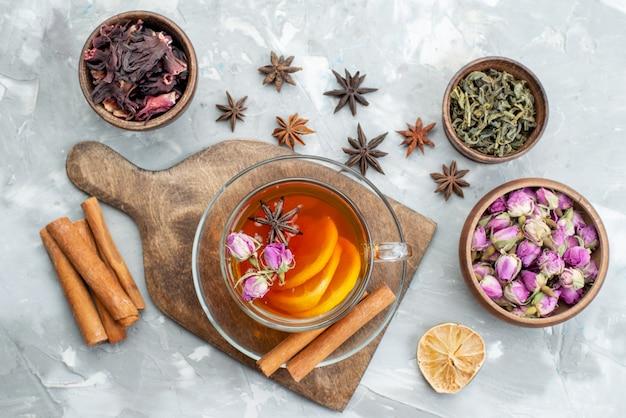 Uma vista de cima, canela e flores, juntamente com uma fatia de limão seco e uma xícara de chá na mesa de flores de frutas secas