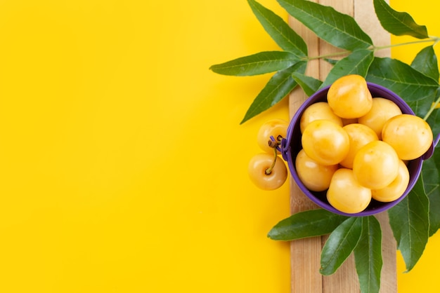 Uma vista de cima cerejas amarelas suaves e doces com folhas verdes em uma mesa amarela, cor de frutas cereja doce de verão