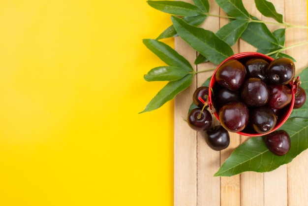 Uma vista de cima cerejas vermelhas maduras e suculentas dentro de uma cesta em uma mesa de madeira marrom e frutas amarelas no verão