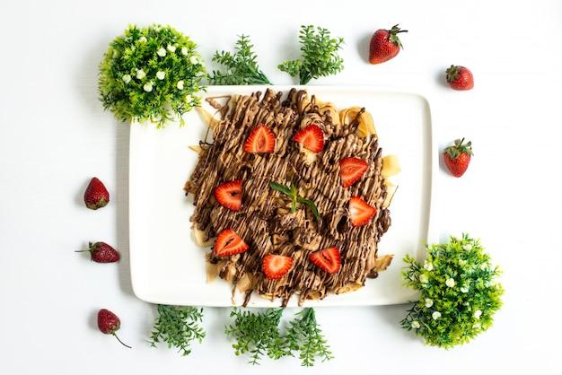 Uma vista de cima, chocolate e morango, sobremesa saboroso, doce com morangos inteiros e plantas espalhadas por todo o fundo branco