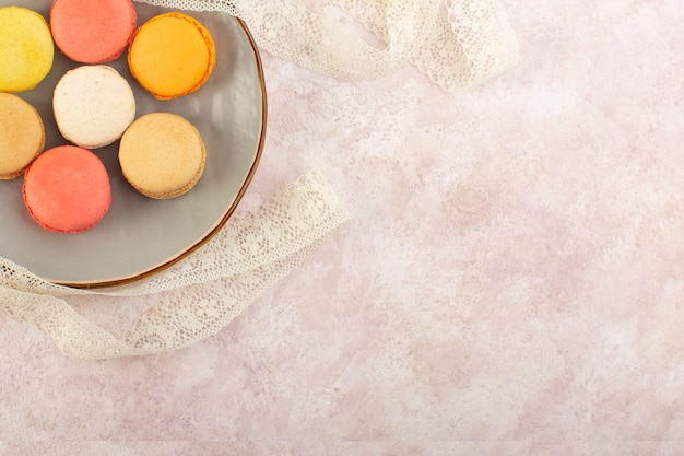 Uma vista de cima coloridos macarons franceses saborosos dentro do prato na mesa rosa bolo biscoito açúcar doce