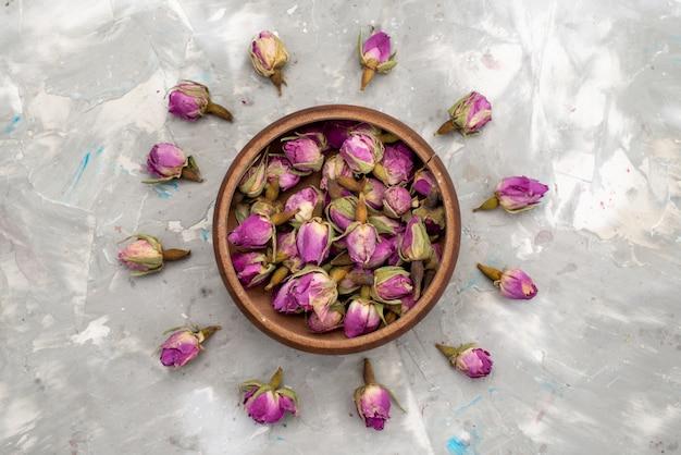 Uma vista de cima com flores roxas dentro de uma tigela redonda e alinhada na foto colorida da planta de flor de mesa clara