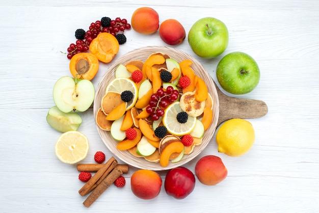 Uma vista de cima com frutas frescas fatiadas coloridas e maduras com frutas inteiras e canela na mesa de madeira e fundo branco.