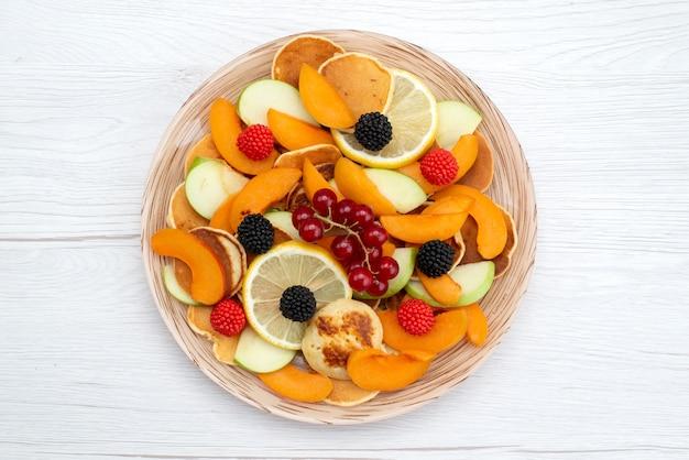 Uma vista de cima com frutas frescas fatiadas coloridas e maduras na mesa de madeira e foto de comida colorida de frutas com fundo branco