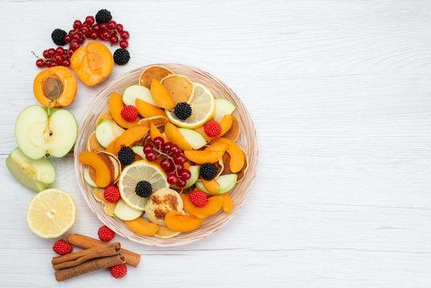 Uma vista de cima com frutas frescas fatiadas coloridas e suaves na mesa de madeira e foto de comida colorida de frutas com fundo branco