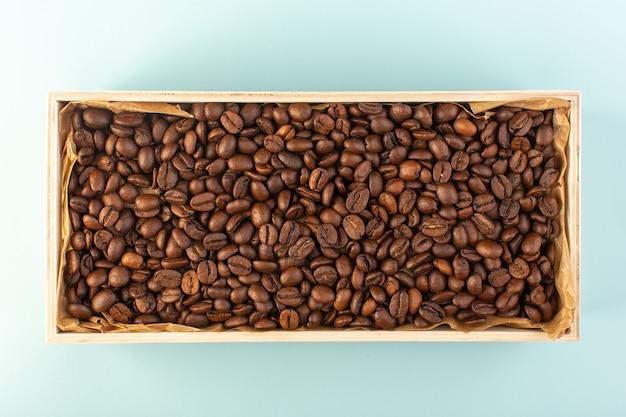 Uma vista de cima com sementes de café marrom dentro da caixa na parede azul copo de café com sementes de bebida