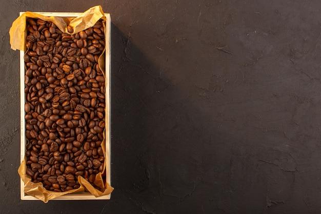 Uma vista de cima com sementes de café marrom dentro da caixa no fundo escuro copo de café com sementes de bebida