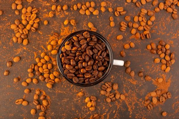Uma vista de cima com sementes de café marrom dentro da tigela na mesa marrom