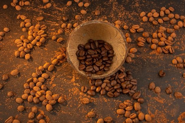 Uma vista de cima com sementes de café marrom dentro e fora da casca do coco na mesa marrom