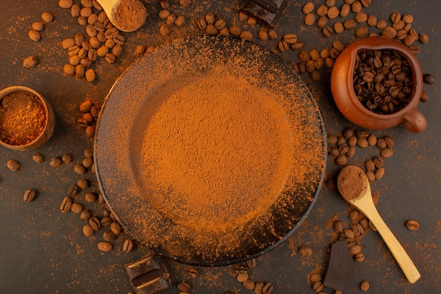 Uma vista de cima com sementes de café marrom junto com uma placa preta cheia de pó de café com barras de chocolate em todo o fundo marrom