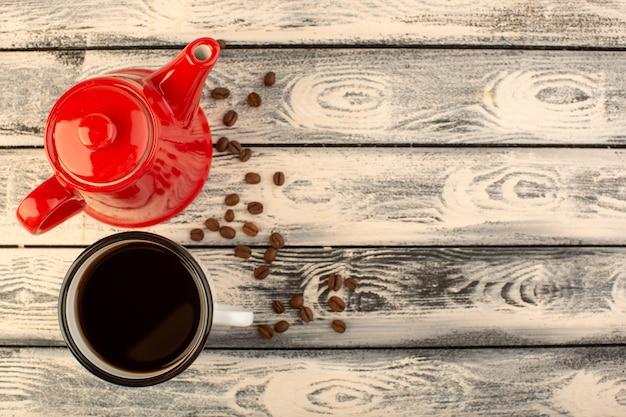 Uma vista de cima da chaleira vermelha com uma xícara de café e sementes de café marrom na mesa rústica cinza beber cor de café