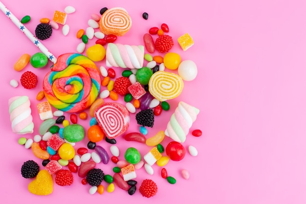 Uma vista de cima da composição de doces coloridos de diferentes cores doces e deliciosas na mesa rosa