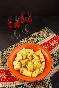 Uma vista de cima da massa italiana cozida saborosa e salgada dentro de um prato redondo de laranja com taças de vinho no tapete projetado e mesa escura