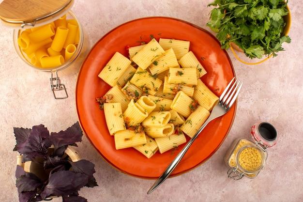 Uma vista de cima da massa italiana cozida saborosa e salgada em um prato redondo de laranja com flores e massa crua na mesa rosa