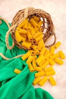 Uma vista de cima da massa italiana crua amarela dentro de uma pequena cesta junto com cordas em tecido verde e rosa