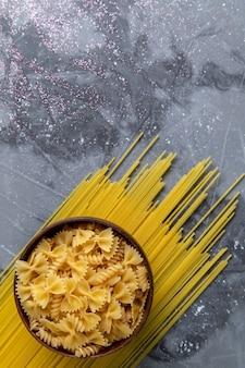Uma vista de cima da massa italiana crua, pequena e longa, formada dentro do prato marrom na mesa cinza.