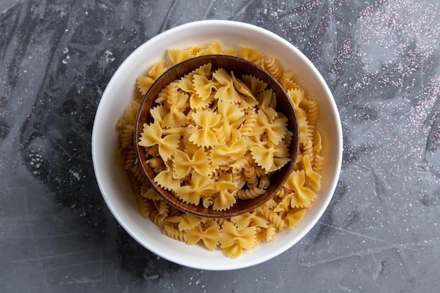 Uma vista de cima da massa italiana crua pouco formada dentro do prato marrom na mesa cinza