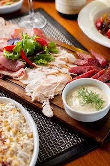 Uma vista de cima das salsichas na mesa com vinho branco e vegetais na mesa restaurante de comida