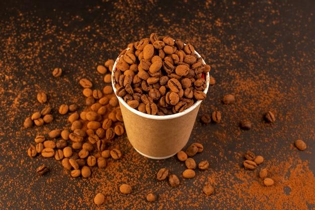 Uma vista de cima das sementes de café marrom dentro de um copo de plástico na mesa marrom